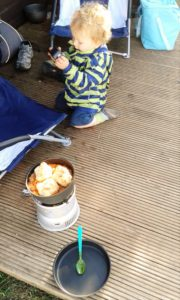 Toddler N plays on the porch outside our camping pod while I cook campfire stew on our Trangia