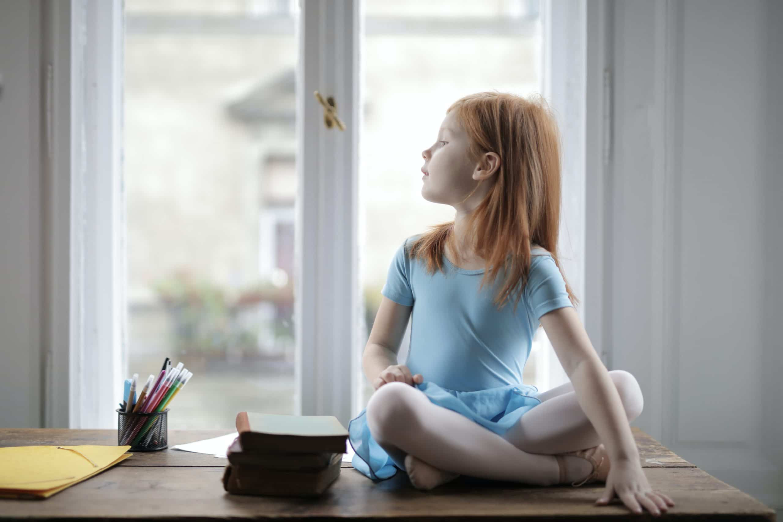 adorable-little-girl-in-ballet-dress-sitting-on-table-3887537